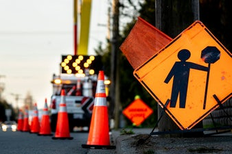 Road work signage and pylons on a roadway.