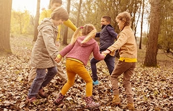 Children holding hands in a circle playing outside in the Autumn.