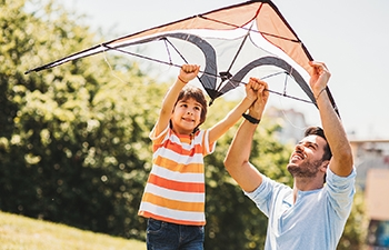 An adult helping a youth to fly a kite.